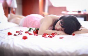 横たわる女性とバラ