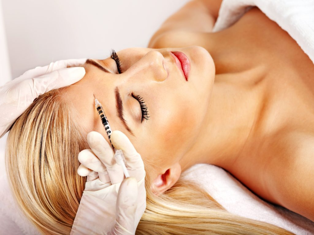 Beauty woman giving botox injections.