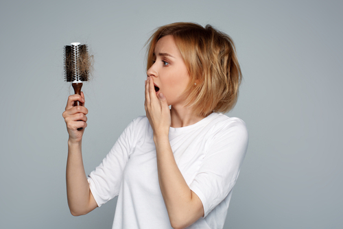 Blonde,Young,Worried,Woman,Holding,Hairbrush,With,Unexpected,Hair,Loss