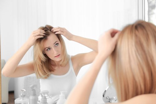 Young,Woman,With,Hair,Loss,Problem,Looking,In,Mirror,At